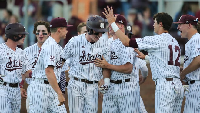 Brent Rooker is congratulated by teammates after hitting a grand slam against Kentucky.