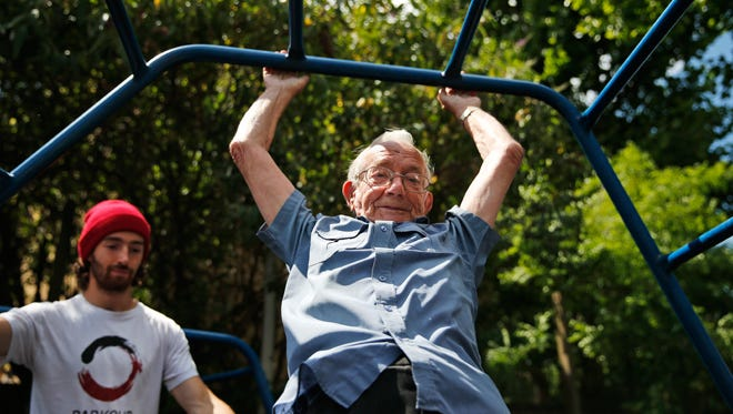George Jackson, 85, tackles the monkey bars during a parkour class for senior citizens in South London.