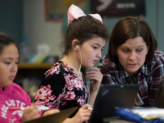 Cynthia Heights Elementary School fourth grade math teacher Jessica Deardurff works with Madelyn Lewis on a factors exercise Wednesday morning.