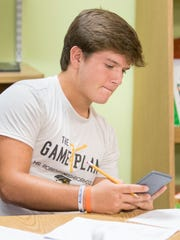 Connor Brasell, of Navarre High School uses his calculator for the math section as he and other student-athletes participating in the Mr. Robbins Neighborhood program take a practice ACT test at Sylvan Learning Center in Pensacola on Saturday, October 14, 2017.