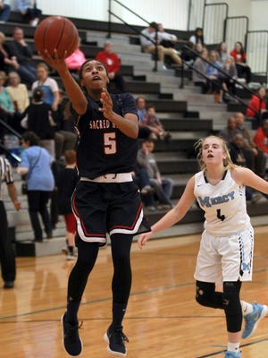 Sacred Heart Academy's Ashlee Harris (5) fights to get her shot off under pressure from Mercy High School's Hope Sivori (5) during the first half of play at Mercy High School in Louisville, Kentucky,       February 12,  2018.