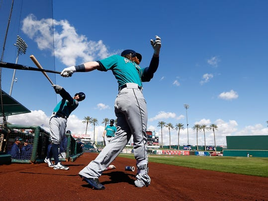 Seattle Mariners' Ben Gamel, right, and Andrew Romine take practice swings as they wait to bat prior to a spring training baseball game against the Cleveland Indians Wednesday, Feb. 28, 2018, in Goodyear, Ariz. (AP Photo/Ross D. Franklin)