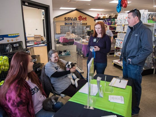 H.E.L.P. the Animals board members Matt and Amy Smith, right, shelter director Sharon McDowell, inner left, and staff member Abby Sanches spend time at the grand opening event for PetSense, 1503 E. Main St., Richmond, on Saturday, April 7, 2018.