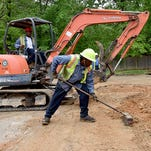 Workers with the city of Jackson Public Works Department repair a broken water line.