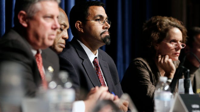 In this October 2013 file photo, state Education Commissioner John King Jr., center, listens to a speaker during a forum on Common Core learning reforms at the Stephen and Harriet Myers Middle School in Albany.