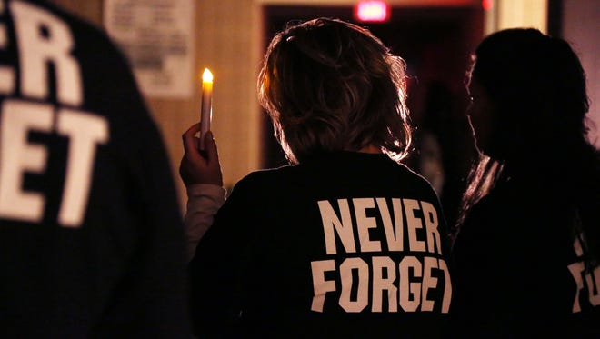 """Family and friends of Brandon Ellingson gather for a vigil to honor him on what would have been his 21st birthday on Sunday at Valley High School in West Des Moines. Many of those in attendance wore black shirts with the number 30 — Brandon's football number — on the front. On the back were the words """"never forget."""""""