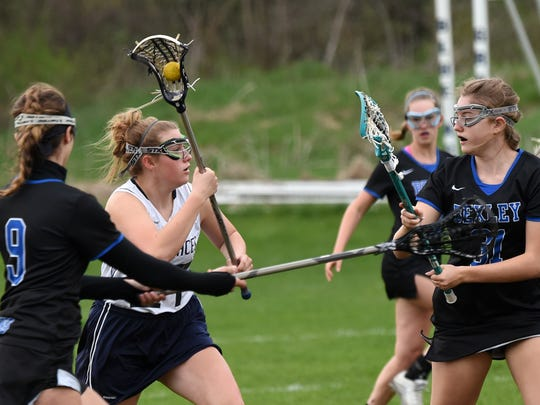 Granville's Danielle Miller looks for an opening around Bexley defenders Sofia Loeser and Emma Dressel. The Blue Aces lost to the Lions 19-10 on Tuesday, April 11, 2017.