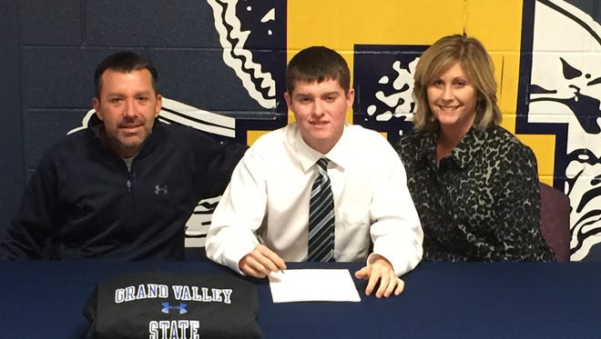 Hartland senior Bryce Messner signs his national letter-of-intent to play golf for Grand Valley State University. He's flanked by his parents, Jay and Shariese.
