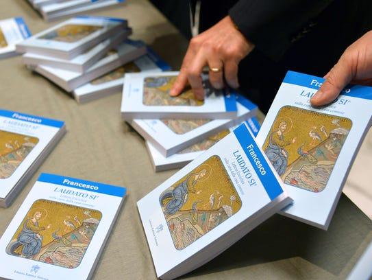 People hold copies of Pope Francis' encyclical, a collection