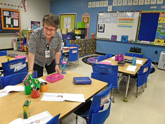 Emily Mitchell straightens items on her students desks