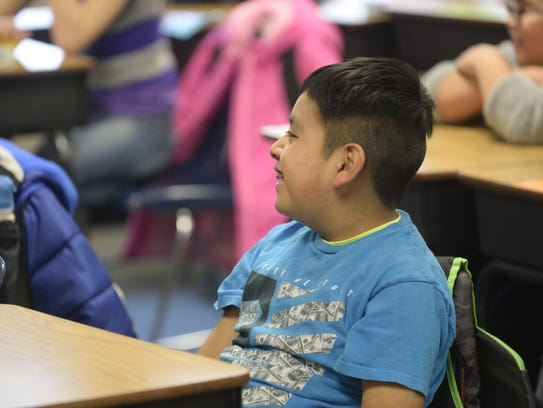 A third-grader laughs during a presentation by Officer