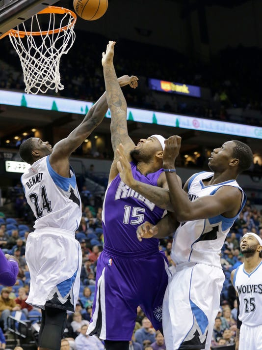 Sacramento Kings center DeMarcus Cousins (15) goes up for a shot between Minnesota Timberwolves forward Anthony Bennett (24) and Timberwolves center Gorgui Dieng, right, of Senegal, during the first quarter of an NBA basketball game in Minneapolis, Saturday, Nov. 22, 2014. (AP Photo/Ann Heisenfelt)