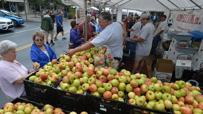 In this Sept. 1, 2017 photo, visitors browse apples at one of the many vendor booths at the N.C. Apple Festival on Main Street in Hendersonville.