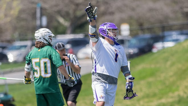 Albany's Tehoka Nanticoke, right, celebrates after a goal as UVM's James Leary looks on during the America East men's lacrosse championship game on Saturday. The Catamounts lost 14-4.