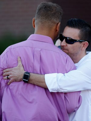 Marcus Weaver, left, a victim of the 2012 shooting at an Aurora, Colo., movie theater, is embraced after Weaver testified during the third day April 29, 2015, in the trial of gunman James Holmes.