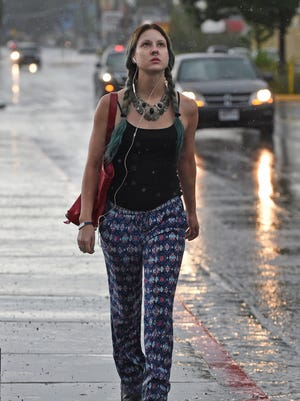 Holly Gazeley watches the rain fall as she walk along Wells Avenue during a thunderstorm on July 8, 2015.