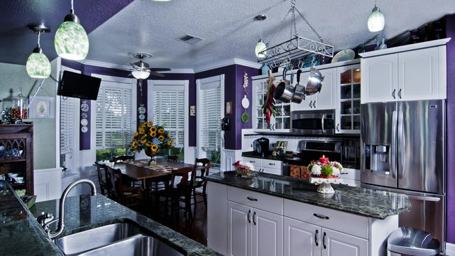Purple walls accent the Coleman's southern living kitchen, which is located smack dab in the center of the house for optimal entertaining. David Hudson on piano and Loyd Have Mercy restaurant will add even more color to the gathering.