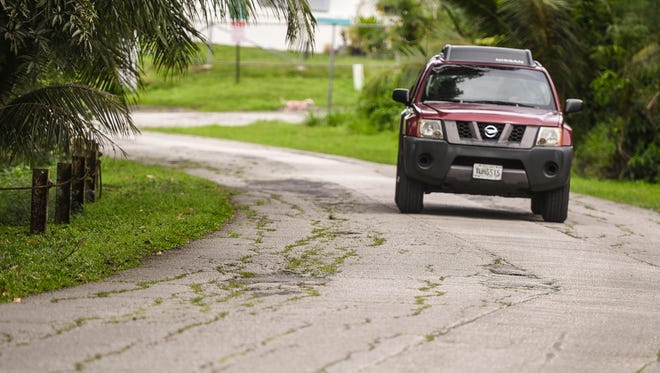 A motorist resorts to travelling in the center of Erskin Drive in Agat, on Thursday, Feb. 9, 2017, to avoid uneven and cracking sections of pavement that riddle the roadway.