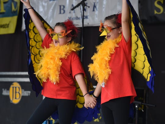 Two young girls dressed in turkey costumes perform in the lip sync contest during the opening day of the 71st Annual Turkey Trot Festival on the downtown square in Yellville.