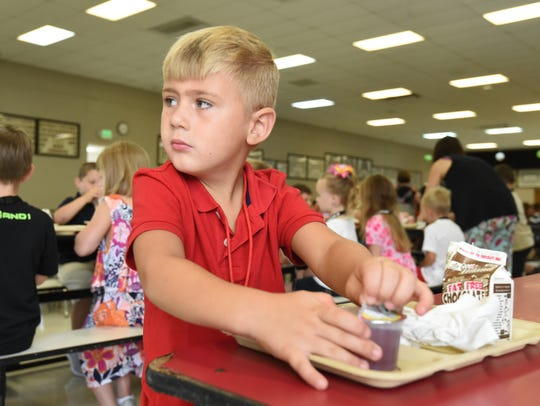 Several children gathered in the school cafeteria to