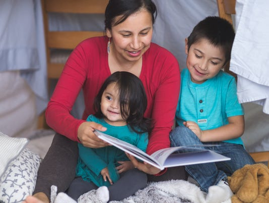 Native American mom reads with her two children under makeshift fort in living room