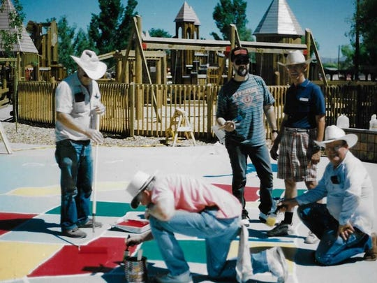 Richard Smith along with other members of the Telephone Pioneers of America work to paint a large map of the United States in Kids' Kingdom shortly after it was built. The project was an effort to help children in the community learnt to identify states.