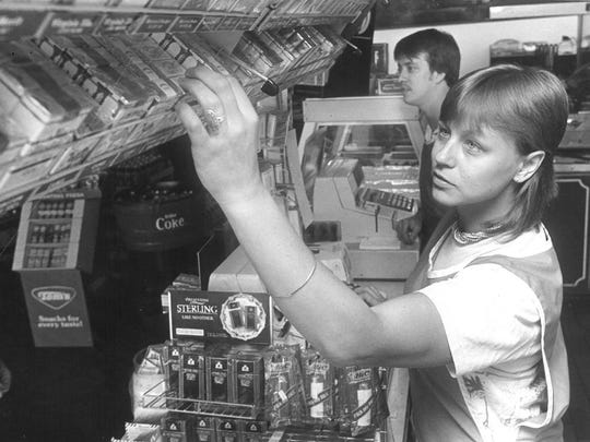 Marcy Clarinda adjusts products at a Jiffy Food Stores in this May 29, 1984, Wichita Falls Record News photograph. Also pictured is Allen Rageur.
