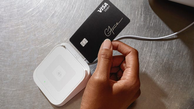 A person inserting a Cash Card debit card into a Square card reader..