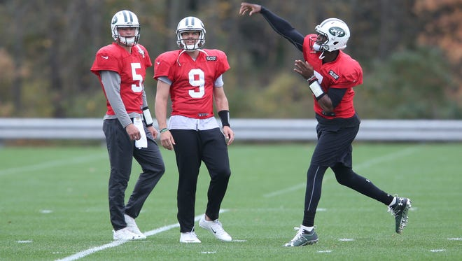 Jets quarterback Geno Smith, right, throws while quartebacks Christian Hackenberg, left, and Bryce Petty watch during NFL football practice in Florham Park, N.J., Thursday, Oct. 20, 2016. Chan Gailey was Todd Bowles' hand-picked offensive coordinator when he was hired as Jets coach last year. After a terrific 2015 season, the Jets are struggling mightily on offense, have switched quarterbacks, and it's on Gailey to get things turned around, and quickly.