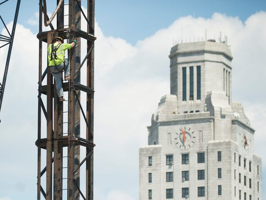 A worker scales a pile driver at the construction site