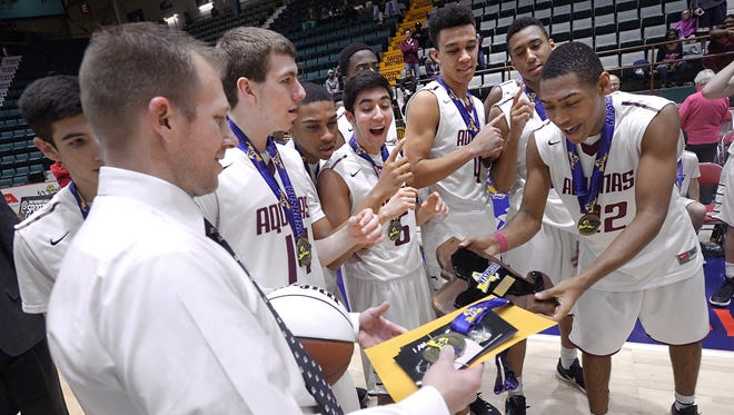 Aquinas head coach Michael Grosodonia, left, hands the NYSPHSAA state championship plaque to Jalen Pickett following the Class AA final of the 2016 NYSPHSAA Boys Basketball Championships held at the Glens Falls Civic Center in Glens Falls, N.Y. on Sunday, March 13, 2016. Aquinas took the Class AA title with a 68-50 win over Middletown-IX.