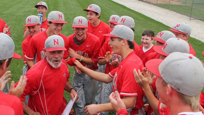 Nixa baseball coach Howard Greenwood (front, left) reacts after receiving a celebratory water bath from his players after they beat Kickapoo 5-2 to win the Class 5 District 11 championship.