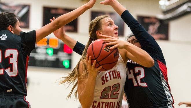 Seton Catholic Prep's Liz Holter(C) (#22) goes up for a shot between Coconino's Kaylee Begay (#23) and Maya Tijerin (#42) during their 4A Conference semifinals game on Wednesday, Feb. 22, 2017, at Copper Canyon High School in Glendale, Ariz.