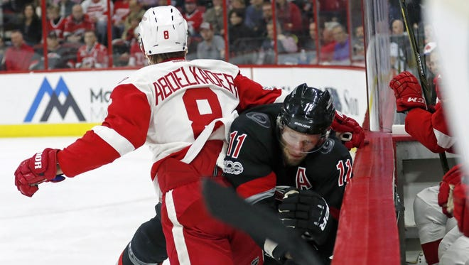 The Hurricanes' Jordan Staal (11) gets checked into the bench by the Red Wings forward Justin Abdelkader (8) during the first period Monday in Raleigh, N.C.