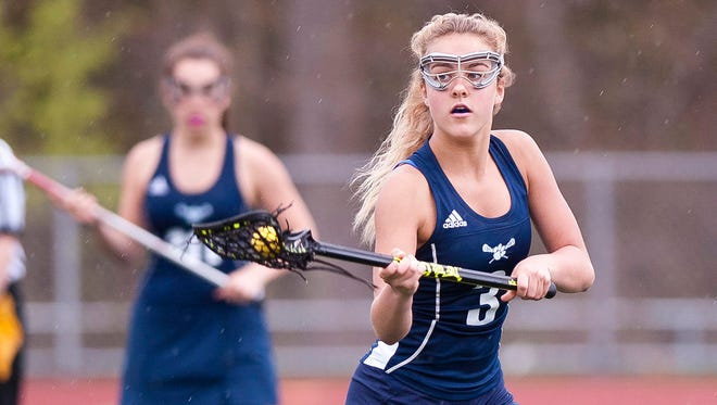 Mount Mansfield's Allison Charland scoops up a loose ball against Burlington during Tuesday's high school girls lacrosse game at Buck Hard Field.