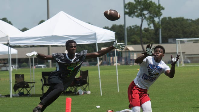 Pine Forest High School's Martin Emerson, right, gets the best of Catholic High School's Tykies Hestle, left, during a 7 on 7 football tournament at Ashton Brosnaham Sports Complex Friday morning June 30, 2017.