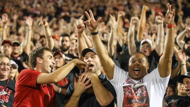 Louisville fans celebrate after catching a Clemson field goal goes wide right and into the stands.
