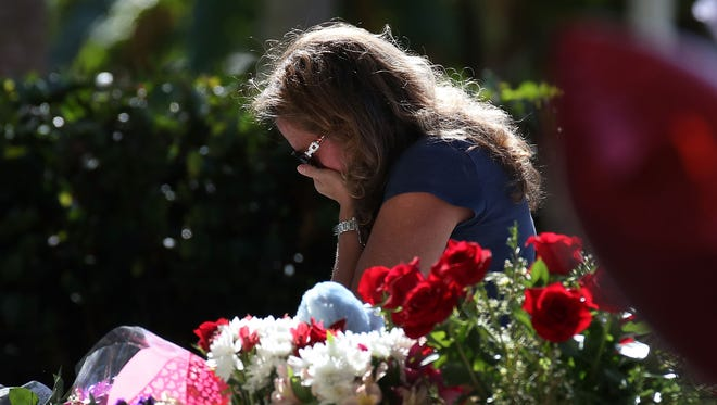 A woman becomes emotional while visiting a temporary memorial at Pine Trails Park on Feb. 17, 2018 in Parkland, Fla.