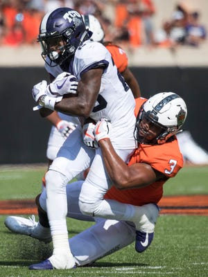 TCU Horned Frogs wide receiver KaVontae Turpin (25) is tackled by Oklahoma State Cowboys linebacker Kenneth Edison-McGruder (3) during the first half at Boone Pickens Stadium.