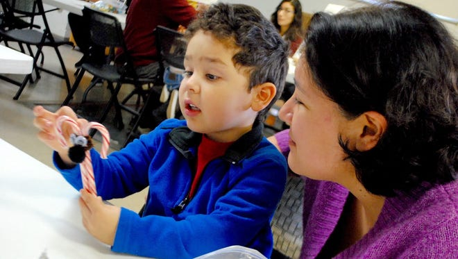 Carlos Flores-Scott, 4, shows his mother, Emma Flores-Scott, how to transform candy canes and pipe cleaners into reindeer.