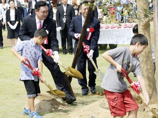 Noraha Mayor Yukiei Matsumoto, rear left, plants a tree with children during an event Saturday in Naraha, Fukushima, northern Japan.