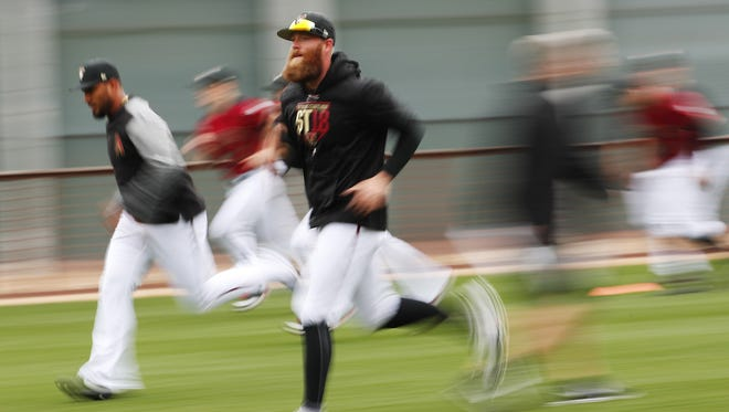 Arizona Diamondbacks relief pitcher Archie Bradley (25) warms up during the first day of workouts for pitchers and catchers at Salt River Fields on the Salt River Pima-Maricopa Indian Reservation February 14, 2018.