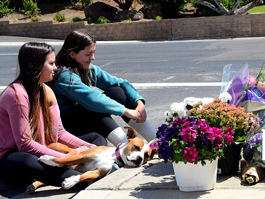 Sierra Donohue, 16, (left) and Shelby Clayton, 16, sit on the street next to the place where their friend, Katie Weingartner, was struck by a vehicle and was killed. The girls spent their afternoon on June 12, 2017 sitting on the street looking at the flowers and photos left behind by Weingartner's friends and family during a vigil the night after the fatal crash.