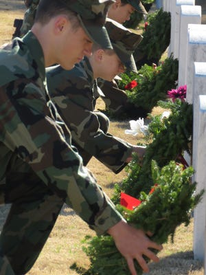 In this photo from last year, Emerald Coast Young Marines place wreaths on the grave markers of those buries in the Barrancas National Cemetery as part of the Wreaths Across America observance aboard NAS Pensacola.