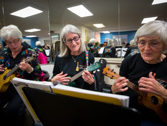 Sandy Clifford, center, a newcomer to playing the ukulele,