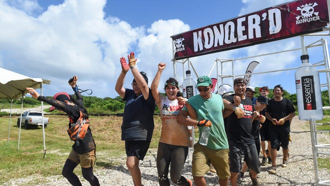 Pacific Daily News' The Score celebrate their finish of the Konqer Obstacle Course Race at the Jose and Herminia Memorial Off-Road Park in Yigo on Nov. 29.