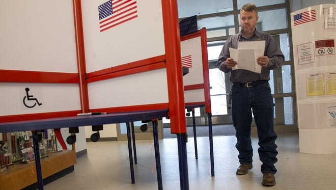 Voter Walter Eaton completes a ballot in February 2017 during an election in Kirtland.