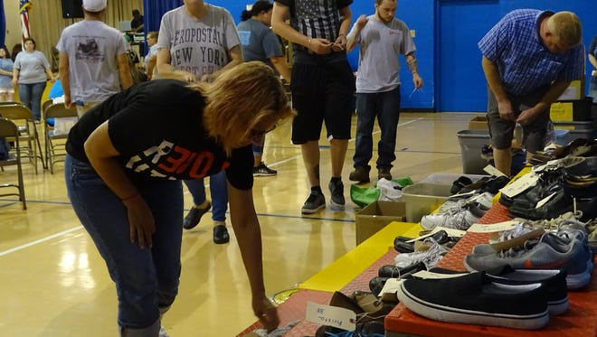People in recovery, friends, and family place shoes during a memorial at the Steps of Change event in the gym at Mt. Logan Elementary on Saturday. The first name and age of 195 Ross County residents who died of an unintentional drug overdose since 2010 were among more than 220 written onto tags and attached to the shoes.