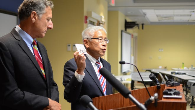 Dr. Harry Chen, commissioner of the Vermont Department of Health, holds up a dose of naloxone, the drug that reduces opioid overdoses, at a news conference Thursday, Aug. 25.