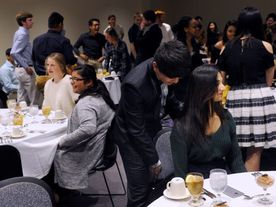 Aanik Tamang seats Seema Shah during an etiquette dinner Thursday at Hardin-Simmons University. The six-course meal was designed to familiarize diners with the customs involved in formal dining.